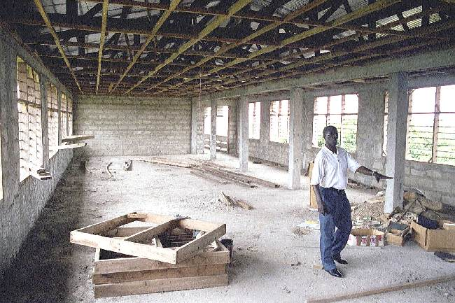 Dr. Obeng - showing third floor Bible College classroom construction progress - October 2000